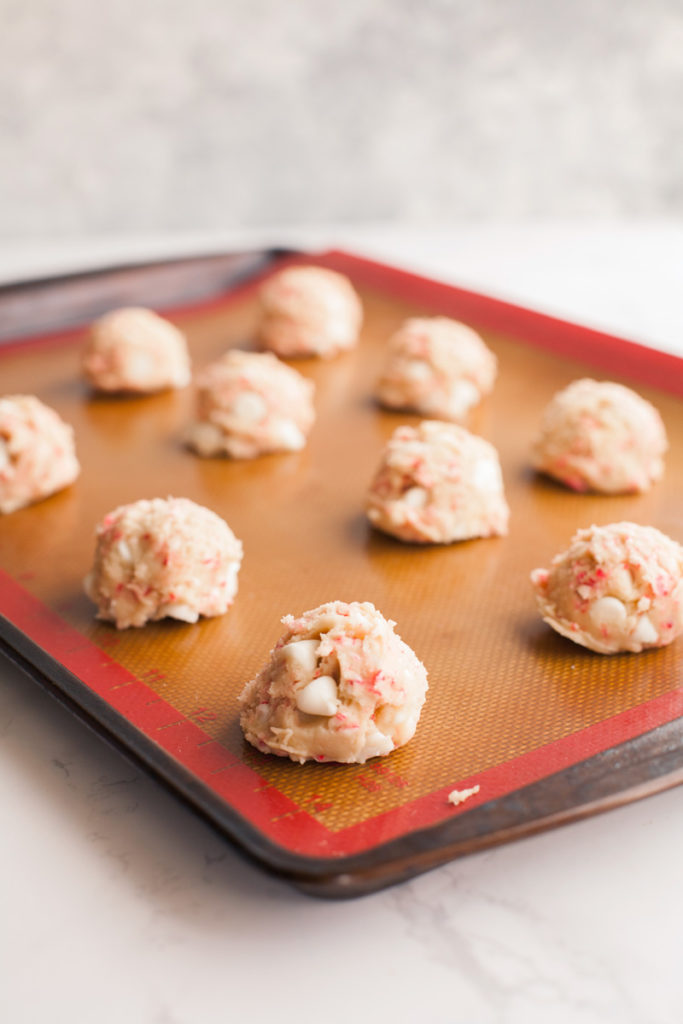 White chocolate candy cane cookie dough on cookie sheet.