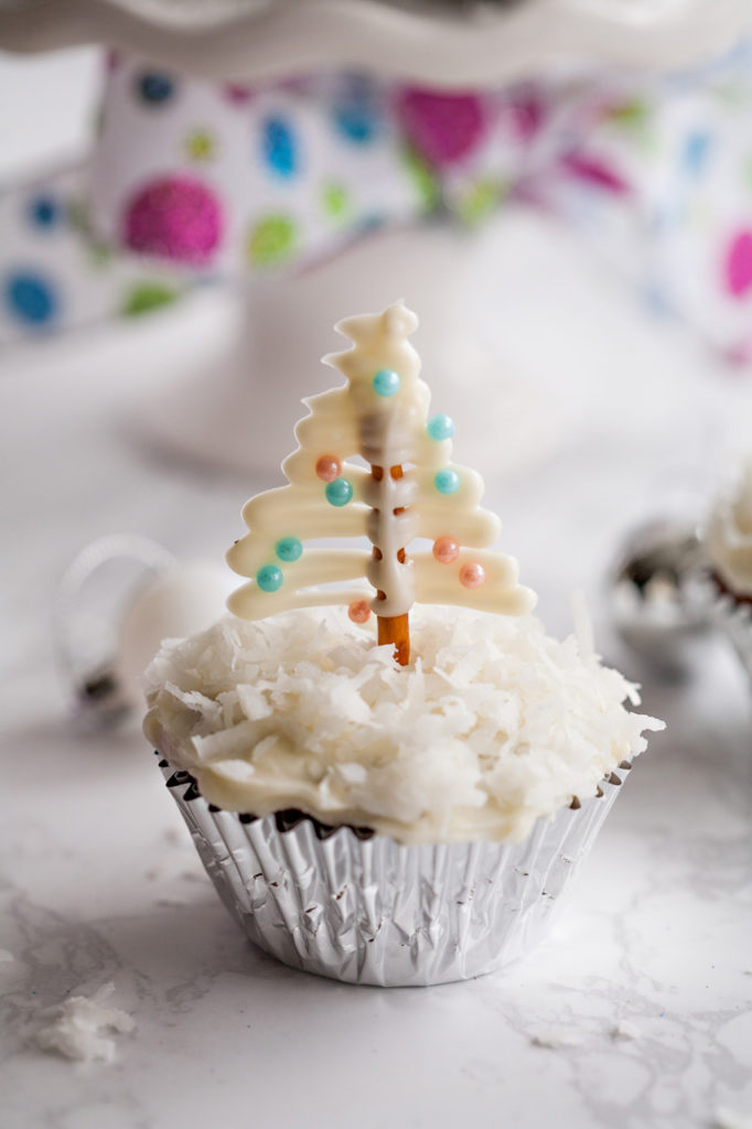 Delicious, festive Gingerbread Cupcakes with Cream Cheese Frosting. Add some cute pretzel Christmas tree toppers on a bed of fluffy coconut!