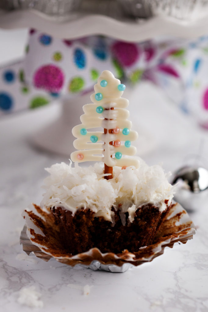 Gingerbread Cupcakes with Cream Cheese Frosting and cute pretzel Christmas tree toppers on a bed of fluffy coconut!