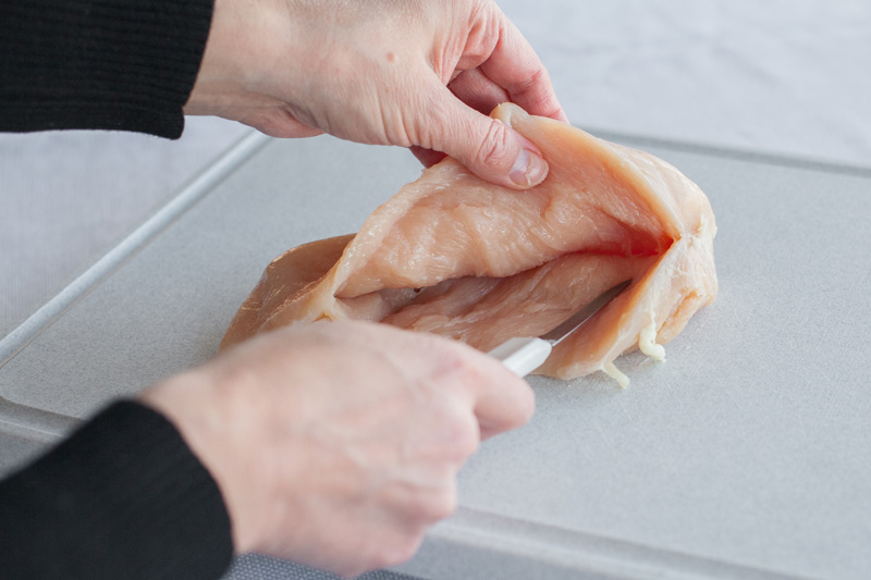 Paring knife cutting a pocket into chicken breast