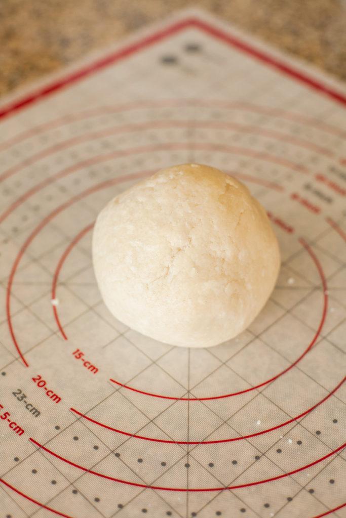 Pie crust dough rolled into a ball on baking mat