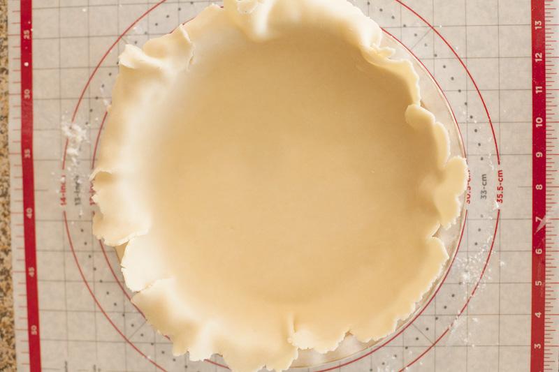 Pie crust dough placed on a pie tin