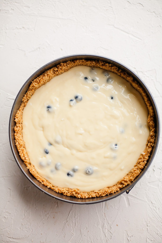 unbaked blueberry cheesecake filling on top of graham cracker crust