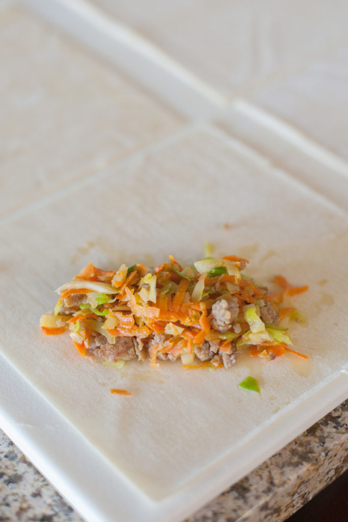The pork filling at the bottom third of the egg roll wrapper.