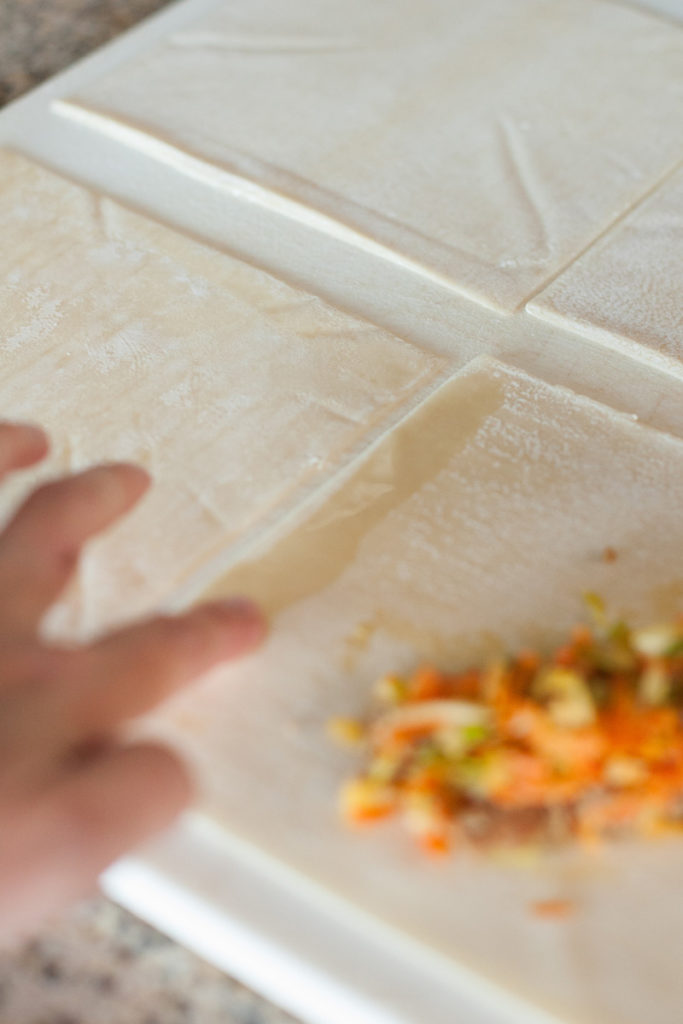 Moistening the edges of the egg roll wrapper with water.