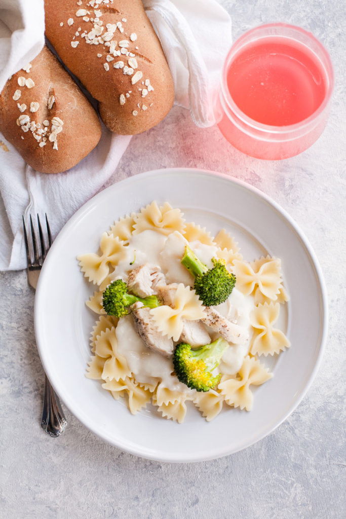 Alfredo sauce on bow tie noodles with chicken and broccoli.